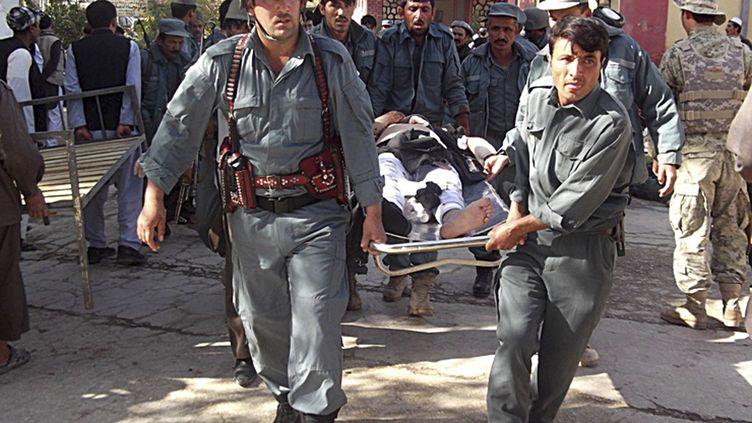 Des soldats afghans évacuant un blessé après un attentat qui a fait au moins 42 morts à Maymana, dans le nord de l'Afghanistan, le 26 octobre 2012. (REUTERS)