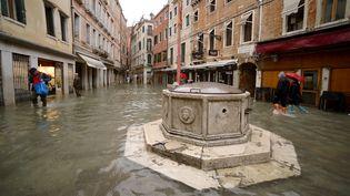 Quelques témérairestraversent la place inondée du Campo Santi Filippo e Giacomo, le 15 novembre 2019 à Venise. (FILIPPO MONTEFORTE / AFP)