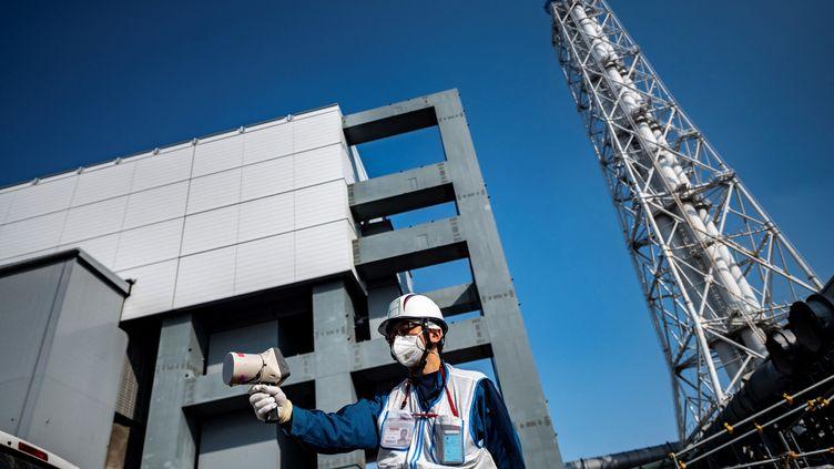 Un employé de la compagnie Tepco mesure le niveau de radioactivité à la centrale de Fukushima (Japon), le 21 février 2021. (PHILIP FONG / AFP)