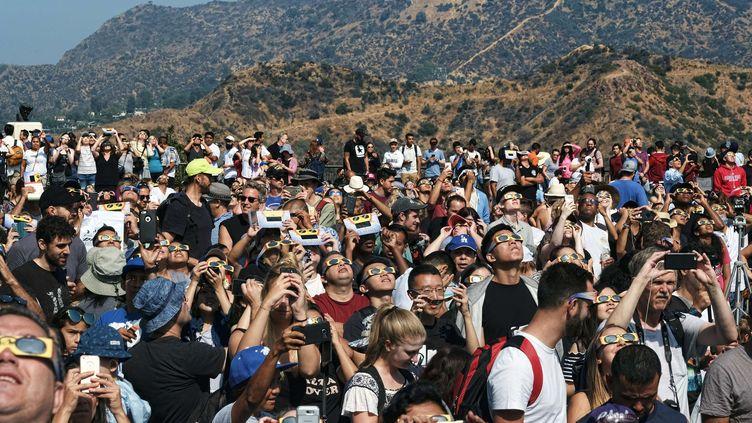"""A Los Angeles, la foule s'est rassemblée dans un observatoire devant le signe """"Hollywood"""" pour observer l'éclipse, le 21 août 2017. (RICHARD VOGEL/AP/SIPA / AP)"""
