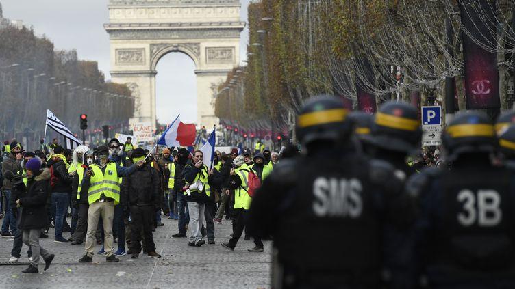 """Casqués, les CRS font face aux """"gilets jaunes"""" près de l'Arc de triomphe. (BERTRAND GUAY / AFP)"""