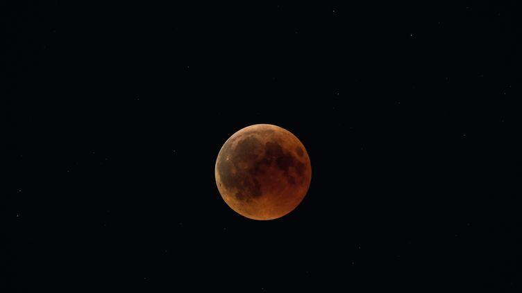 Une photo de la Lune lors de la précédente éclipse, le 27 juillet 2018 au-dessus d'Athènes (Grèce). (ARIS MESSINIS / AFP)