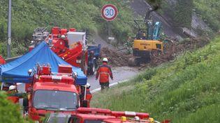 Des travailleurs déblaient la route après un glissement de terrain, à Zushi (Japon), le 3 juillet 2021. (KENTARO TOMINAGA / YOMIURI  / AFP)