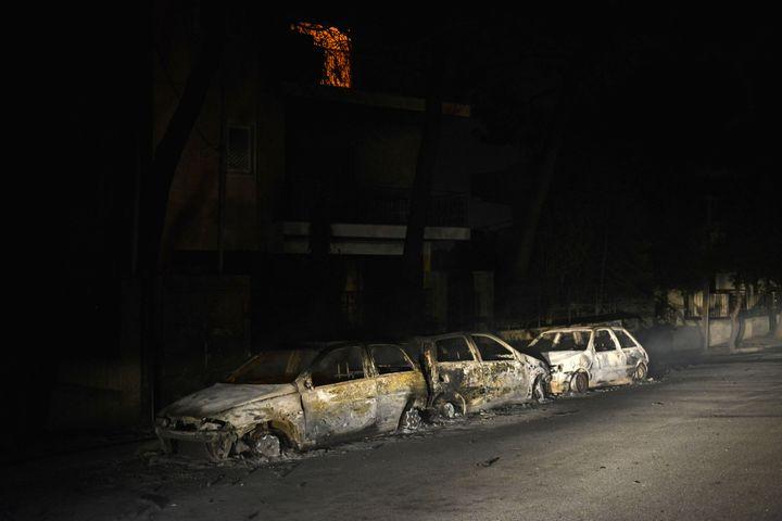 Des voitures brûlées le 23 juillet 2018 à Mati (Grèce). (ANGELOS TZORTZINIS / AFP)