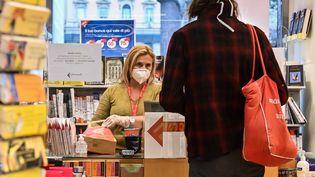 Une caissière dans une librairie à Rome (Italie), le 20 avril 2020. (ANDREAS SOLARO / AFP)