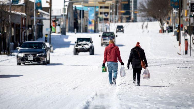 Des habitants d'Austin, au Texas, marchent dans la neige qui a recouvert la ville, lundi 15 février 2021. (MONTINIQUE MONROE / GETTY IMAGES NORTH AMERICA / GETTY IMAGES VIA AFP)