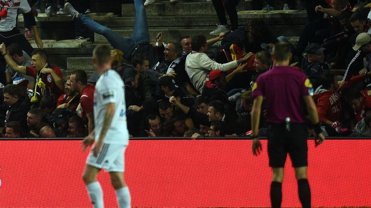 Les fans du Losc s'agglutinent en bas de la tribune et font céder le grillage séparant la tribune latérale de la pelouse. (FRANCOIS LO PRESTI / AFP)