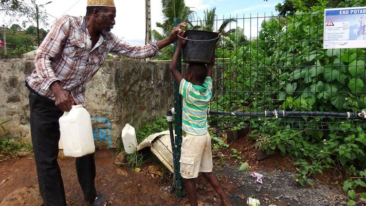 Des habitants remplissent des bidons à un point d'eau potable à Tsararano (Mayotte), le 27 décembre 2017. (ORNELLA LAMBERTI / AFP)