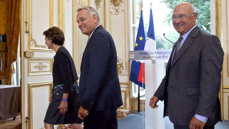 Le Premier ministre, Jean-Marc Ayrault (C), avec le ministre du Travail, Michel Sapin (D), après la présentation de la réforme des retraites, le 27 août 2013 à Matignon. (KENZO TRIBOUILLARD / AFP)