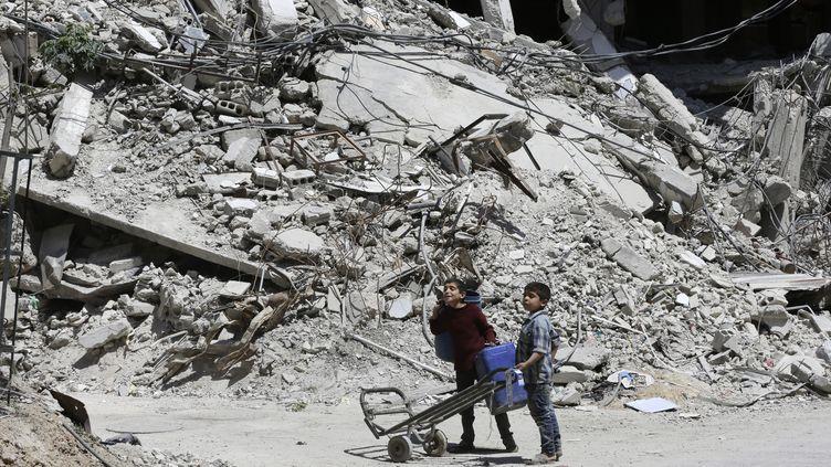 Deux enfants au milieu des ruines de Douma, dans la Ghouta orientale (Syrie), le 16 avril 2018. (LOUAI BESHARA / AFP)