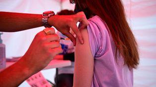 Une adolescente reçoit une dose de vaccin contre le Covid-19 à Paris, le 29 juin 2021. (MARTIN BUREAU / AFP)