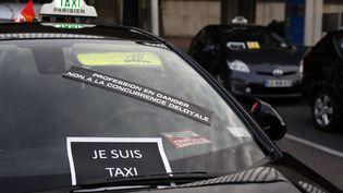 """Une pancarte """"Je suis taxi"""" est apposée sur un taxi parisien, mobilisé contre UberPop, le 25 juin 2015, à l'aéroport de Paris-Orly. (THOMAS SAMSON / AFP)"""