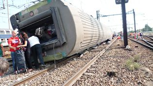 Une voiture du train Paris-Limoges, couchée sur le flanc en gare de Brétigny-sur-Orge (Essonne), le 13 juillet 2013, au lendemain de l'accident. (A.J.CASSAIGNE/PHOTONONSTOP / PHOTONONSTOP)