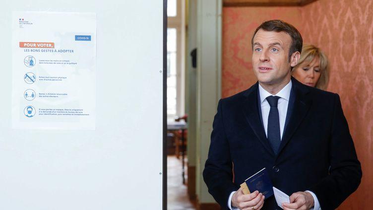 Emmanuel Macron et son épouse Brigitte Macron entrent dans des isoloirs d'un bureau de vote du Touquet (Pas-de-Calais) au premier tour des élections municipales, le 15 mars 2020. (PASCAL ROSSIGNOL / REUTERS)