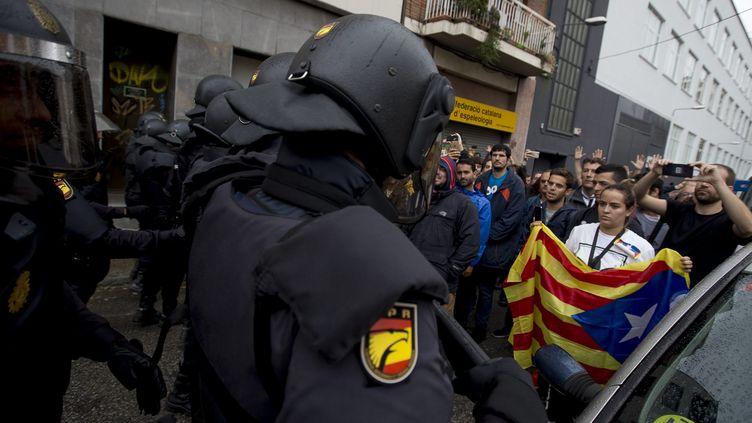 Desmilitants favorables à l'indépendance de la Catalogne font face à la police espagnole, le 1er octobre 2017, à Barcelone. (ALBERT SALAM / NOTIMEX / AFP)
