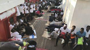 """Des migrants sur le navire """"Ocean Viking"""" exploité par les ONG françaises SOS Méditerranée et Médecins sans Frontières (MSF),le 12 août 2019. (ANNE CHAON / AFP)"""