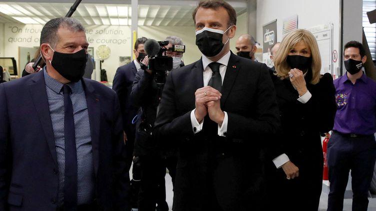 Emmanuel Macron, accompagné de son épouse Brigitte, se tient aux côtés de Michel Catalano dans l'imprimerie de ce dernier à Dammartin-en-Goële, le 11 mars 2021. (GONZALO FUENTES / AFP)