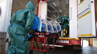 Des hommes d'une unité spéciale équipés de combinaisons de protection en exercice de démonstration de l'évacuation d'un malade du Covid-19 à Prétoria, en Afrique du Sud, le 4 mai 2020. (PHILL MAGAKOE / AFP)