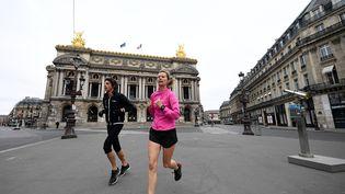 Une femme fait son jogging sur la place de l'Opéra à Paris, le 21 mars 2020. (FRANCK FIFE / AFP)
