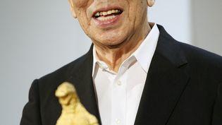 L'acteur japonaisHaruo Nakajima brandit une statue de Godzilla, le 19 juillet 2014 à Tokyo, au Japon. (STR / JIJI PRESS)