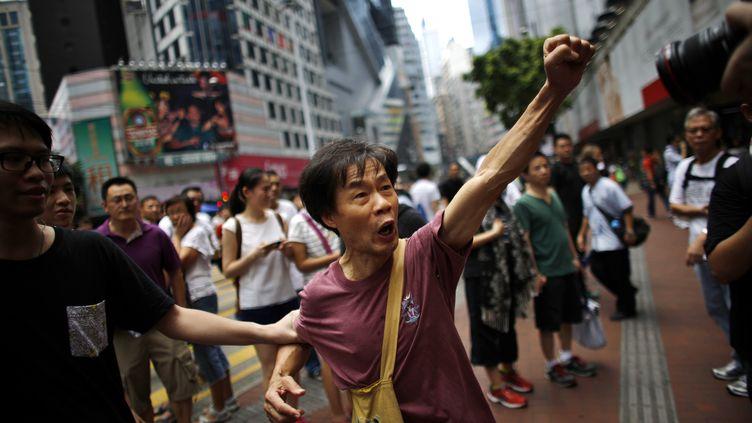 Après quatre jours de manifestation, la tension est parfois vive entre les militants pro-démocratie et les pro-Pékin. Devant le siège du gouvernement, un démocrate apalgue un soutien du régime. (CARLOS BARRIA / REUTERS)