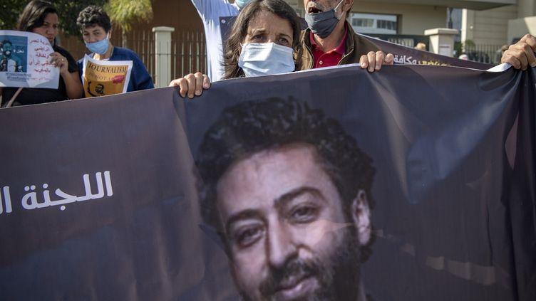 La mère d'Omar Radi tient une banderole lors d'une manifestation de soutien pour son fils journaliste qui comparait devant la justice marocaine à Casablanca, le 22 septembre 2020. (FADEL SENNA / AFP)