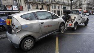 Une Autolib' embarquée par une fourrière, le 28 mars 2017, dans le 6e arrondissement, à Paris. (SERGE ATTAL / ONLY FRANCE / AFP)