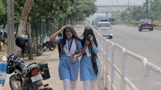 Des étudiantes se couvrent le visage pour se protéger du soleil, le 31 mars 2021 à Bhubaneswar (Inde). (NURPHOTO / AFP)