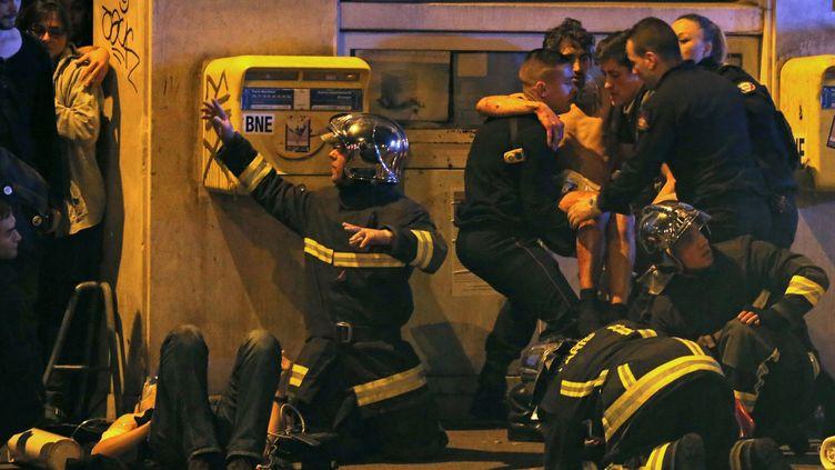 Des pompiers s'occupent de blessés devant la salle de concert Le Bataclan, à Paris, vendredi 13 novembre 2015. (CHRISTIAN HARTMANN / REUTERS)
