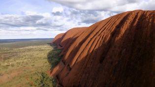Un gigantesque bloc de roche pourpre, aux accents quasi mystiques, s'impose dans l'espace australien. (FRANCE 2)