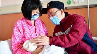 Deux parents vêtus de masques pour lutter contre le nouveau coronavirus enlacent leur nouveau-né à l'hôpital deTaiyuan, dans le nord de la Chine, le 5 février 2020. (CAO YANG / XINHUA / AFP)