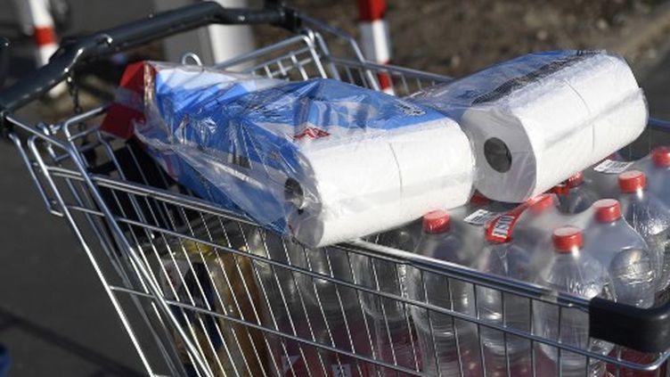 Un charriot rempli de packs d'eau et de rouleauxde papier toilette. (INA FASSBENDER / AFP)