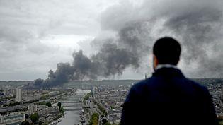 Un homme regarde le panache de fumée s'élever au dessus de Rouen (Seine-Maritime), le 26 septembre 2019. (PHILIPPE LOPEZ / AFP)