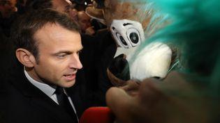 Emmanuel Macron est interpellé par des mascottes des Jeuns Agriculteurs au Salon de l'agriculture à Paris, le 24 février 2018. (LUDOVIC MARIN / AFP)
