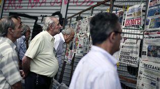 Des Grecs lisent les unes des journaux, dans le centre d'Athènes, le 22 juin 2015. (LOUISA GOULIAMAKI / AFP)