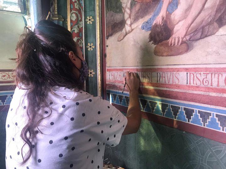 Une restauratrice à l'oeuvredans la chapelle Sainte-Geneviève, dans l'église Saint Séverin à Paris.  (LOU BOURDY / RADIO FRANCE)