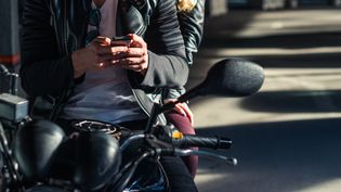 Motard utilisant un smartphone (photo d'illustration) (GETTY IMAGES)