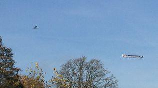 """Un avion de tourisme tirant une banderole """"Hollande démission"""" a survolé, le 11 novembre 2014, le mémorial de Notre-Dame-de-Lorette, àAblain-Saint-Nazaire (Pas-de-Calais), consacré à la première guerre mondiale. (CAROLINE THEBAUD / FRANCE 2)"""
