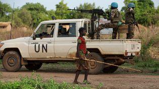 Une jeune fille passe devant une patrouille de casques bleus dans le village de Bambara en République centrafricaine le 25 avril 2017. (BAZ RATNER / X02483)