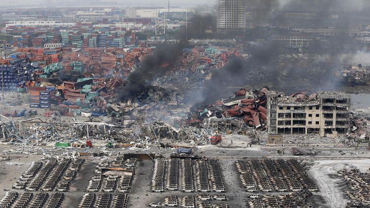 De la fumée s'échappe de containers alors que les pompiers luttent encore contre les feux provoqués par des explosions sur un site industriel de Tianjin (Chine), le 14 août 2015. (  REUTERS)