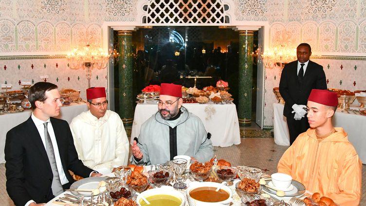 Le roi du Maroc Mohamed VI (C) et son fils, le prince héritier Moulay Hassan (D), partageant l'Iftar, dîner de rupture du jeûne du ramadan, avec Jared Kushner (G), principal conseiller du président américain Donald Trump, le 28 mai 2019 au palais royal de Salé (Rabat). (- / MOROCCAN ROYAL PALACE)