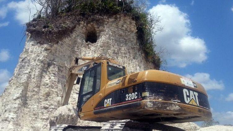 Au nord du Belize, le 10 mai 2013, une pelleteusedevant une ruine archéologique du sitemayaNoh Mul, détruite pour en faire des gravats afin de réparer des routes. (Jules Vasquez / AFP )