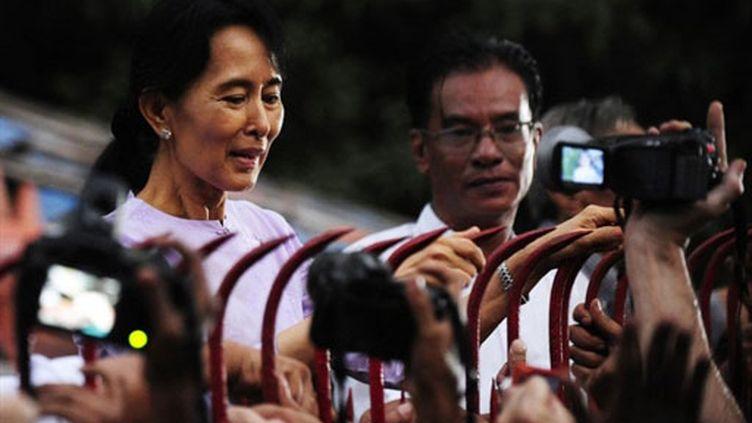 Aung San Suu Kyi apparaît à la grille de sa maison après l'annonce de sa libération (13 novembre 2010) (AFP)