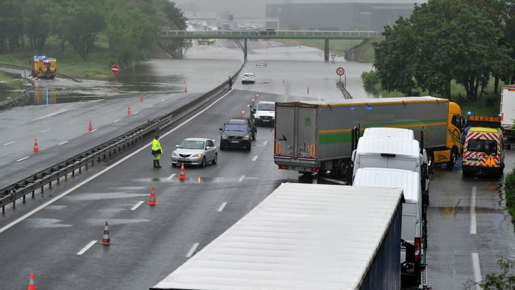 Des véhicules évacuent une portion de l'A10 inondée à hauteur de Saranaprèsles fortes précipitations qui ont touché le Loiret, mardi 31 mai 2016. (GUILLAUME SOUVANT / AFP)