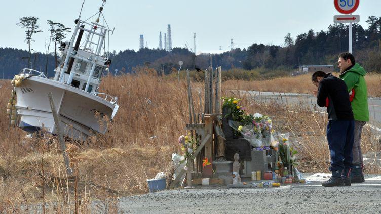 Deux hommes se recueillent près de la centrale nucléaire de Fukushima (Japon), le 11 mars 2014, trois ans après le séisme et le tremblement de terre qui avaient frappé le littoral. (YOSHIKAZU TSUNO / AFP)