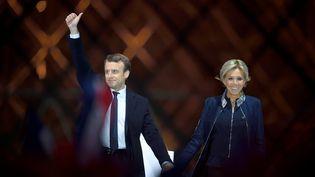 Emmanuel Macron, accompagné de son épouse Brigitte, célèbre sa victoire face à Marine Le Pen lors du second tour de l'élection présidentielle, le 7 mai 2017 devant la pyramide du Louvre, à Paris. (ERIC FEFERBERG / AFP)