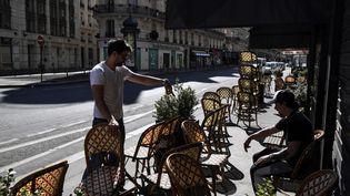Des restaurateurs préparent la réouverture de la terrasse de leur établissement, le 31 mai 2020, à Paris. (ALAIN JOCARD / AFP)