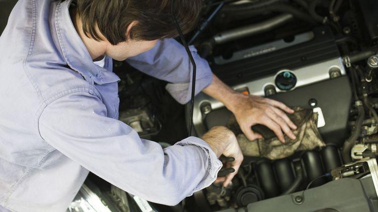 Un salarié travaille sur le moteur d'une automobile. Photo d'illustration. (MAXPPP)