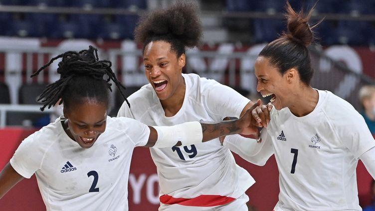 Meline Nocandy (à gauche), Oceane Sercien Ugolin (au centre) et Allison Pineau (à droite) après la victoire de l'équipe de France de handball en demi-finale des Jeux olympiques de Tokyo. (FABRICE COFFRINI / AFP)