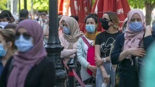 Des personnes portant des masques font la queue devant les magasins après le déconfinement partielà Tunis, le 11 mai 2020. (YASSINE GAIDI / ANADOLU AGENCY)